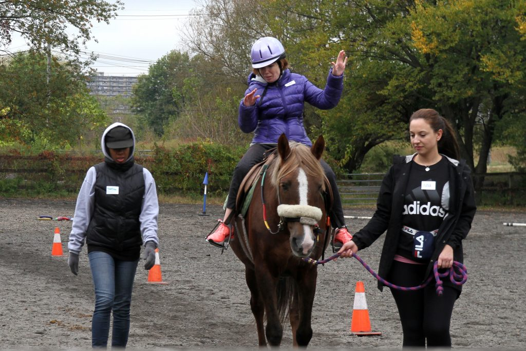 Rider Jeanne, wearing a purple jacket and riding helmet, sits on a horse with a white blaze on his nose. Jeanne participates in a balancing activity, hands up in the air. She is assisted by two volunteers, one lead walking the horse and the other spotting.